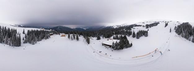 Atemberaubendes panorama von sanften hügeln und bergen im schnee mit touristenlagern an einem wolkigen wintertag