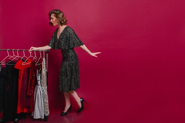 Atemberaubendes schlankes mädchen in den trendigen schuhen, die nahe kleiderbügeln stehen und kleidung wählen