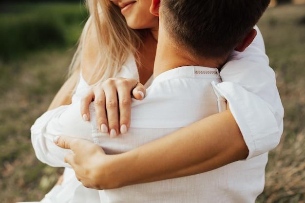 Atemberaubendes, sinnliches nahaufnahmeporträt des jungen glücklichen paares, das umarmt. mann küsst leidenschaftlich seine freundin auf den hals. fokus auf mannhals, weicher fokus.