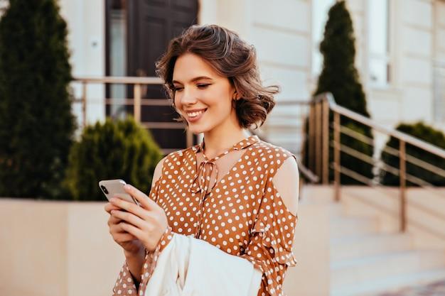 Atemberaubendes weibliches modell in der eleganten bluse, die telefonbildschirm mit interessiertem gesichtsausdruck betrachtet. außenaufnahme der erfreuten europäischen frau in der braunen kleidung, die sms mit lächeln sendet.