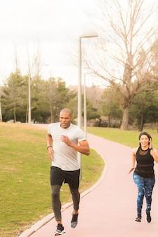 Athetisches paar, das auf fußweg im park läuft. multiethnische menschen, die im freien trainieren.
