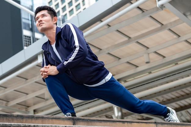 Athlet asiatischer mann in der laufenden starthaltung auf der stadtstraße.