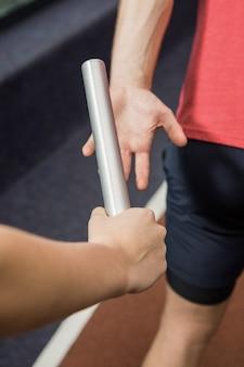 Athlet, der dem partner einen taktstock übergibt