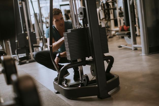Athlet, der die gewichtsplatten, bereitend für sein gewichtheben-training an der turnhalle hinzufügt