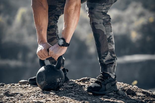 Athlet, der gewicht hebt. naturlandschaft. selektiver fokus. zugeschnittenes foto.