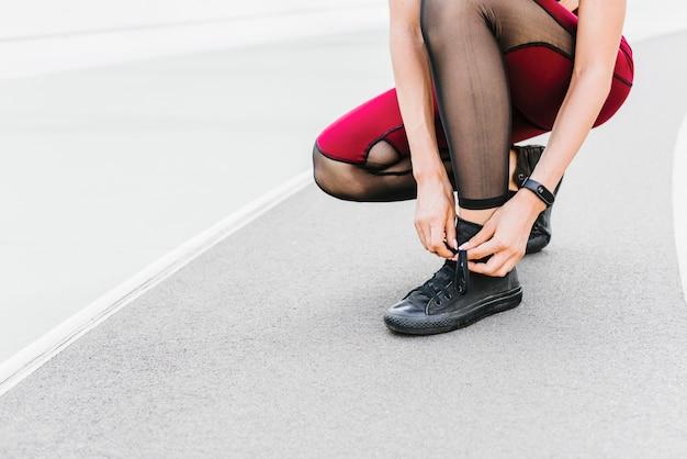 Athlet, der ihre schnürsenkel bindet