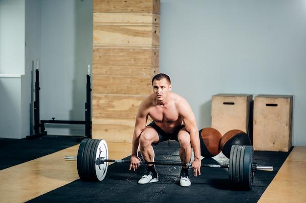 Athlet, der schwarze shorts trägt, die große langhantel heben