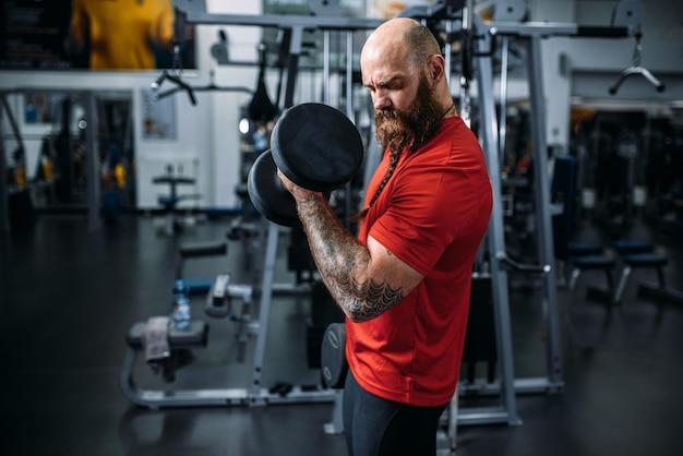 Athlet, der übung mit hanteln im fitnessstudio macht