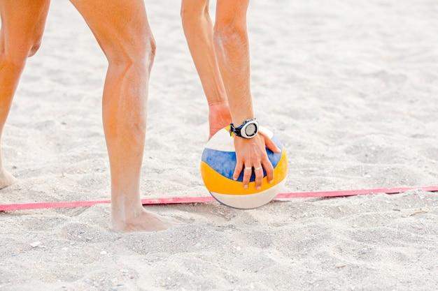 Athlet, der volleyball am strand hält
