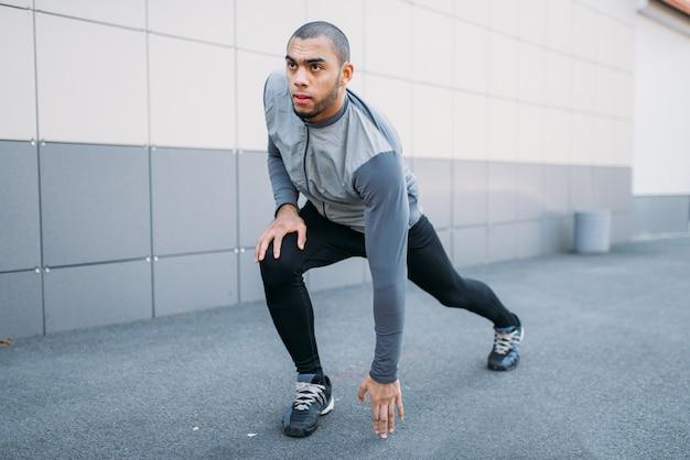 Athlet, der vor dem laufen dehnübungen macht. jogger am morgendlichen fitnesstraining. läufer in sportbekleidung beim training im freien