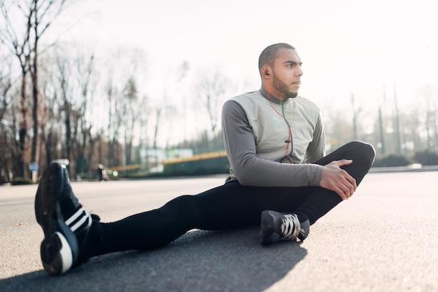 Athlet, der vor dem laufen dehnübungen macht