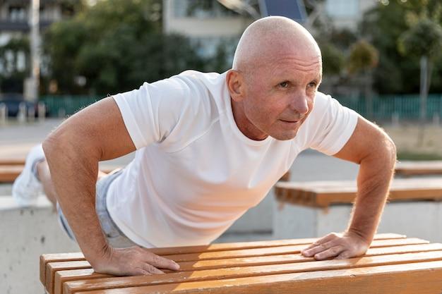 Athlet des älteren mannes, der liegestütze tut