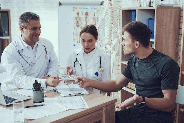 Athlet gibt den doktoren in der klinik geld