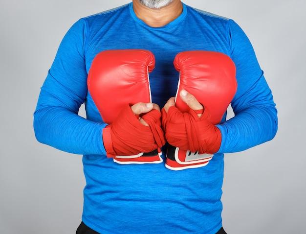 Athlet in der blauen kleidung, die ein paar lederne boxhandschuhe hält
