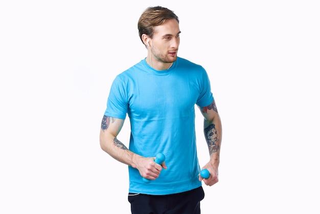 Athlet in einem blauen t-shirt mit hanteln in der handübung