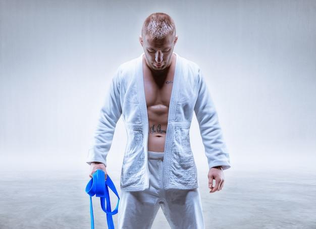 Athlet in einem kimono mit blauem gürtel steht mit gesenktem kopf. das konzept von karate und judo. gemischte medien