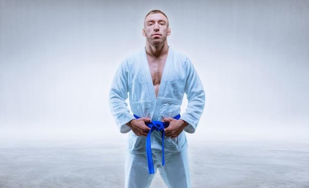 Athlet in einem kimono mit einem blauen gürtel steht auf einem hellen hintergrund. das konzept von karate und judo. gemischte medien