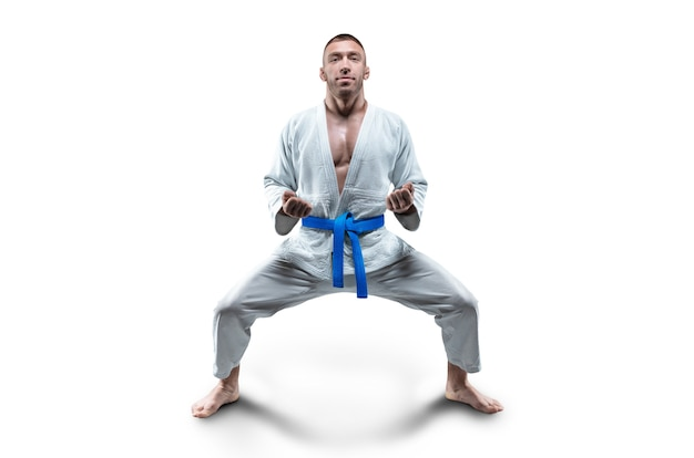 Athlet in einem kimono mit einem blauen gürtel steht in einer kampfposition. konzept von karate, sambo, jujitsu. gemischte medien