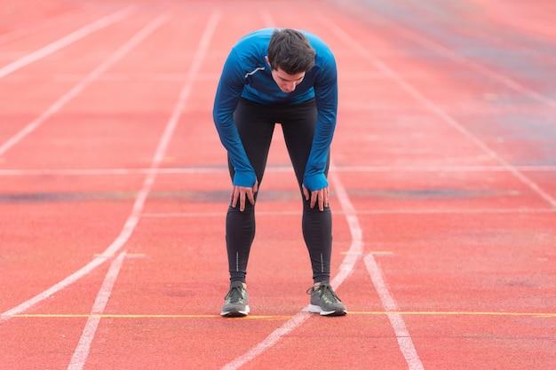 Athlet junger mann müde, auf laufbahn ruhend.