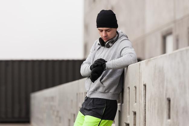 Athlet lehnte sich gegen eine wand und schaute auf die uhr