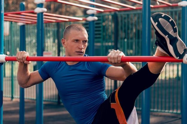Athlet macht dehnübungen training auf sportplatz