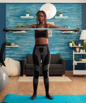 Athlet macht heimtraining im wohnzimmer mit gummiband auf yogamatte für rückenmuskulatur