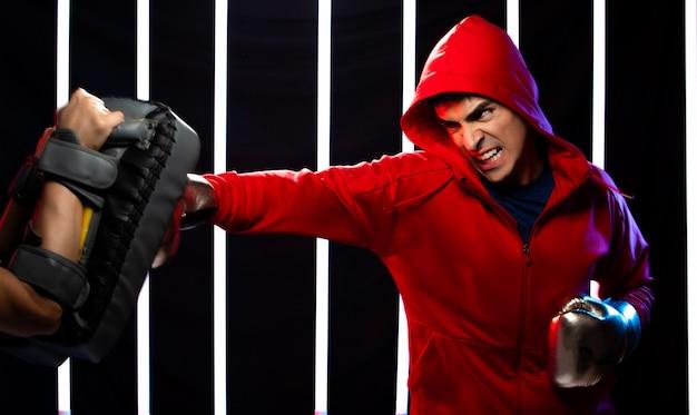 Athlet mann, der boxsport im modernen fitnessstudio trainiert
