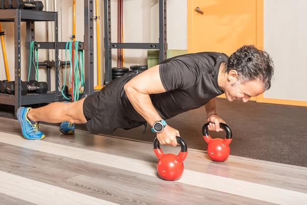 Athlet mann macht liegestütze mit kettlebells im fitnessstudio. konzept der übung mit geräten im fitnessstudio.