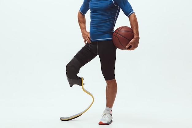 Athlet mit behinderungen oder amputierter isoliert auf weißem studioraum. professioneller männlicher basketballspieler mit beinprothesentraining und üben im studio.