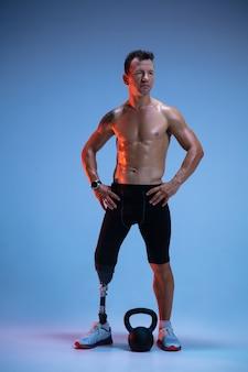 Athlet mit behinderungen oder amputierter lokalisiert auf blauem studiohintergrund. professioneller männlicher sportler mit beinprothesentraining mit gewichten in neon.