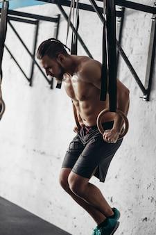 Athlet mit körperübungen in einem fitnessstudio