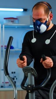 Athlet mit maske und elektroden am körper, der auf einem crosstrainer im wissenschaftssportlabor zur überwachung des gesundheitszustands läuft