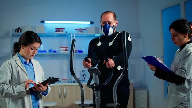 Athlet mit maske und elektroden beim körpertraining mit crosstrainer, während der sportwissenschaftler mit dem tablet interagiert und den ekg-status überwacht