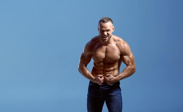 Athlet mit muskulösem körper zeigt bizeps im studio