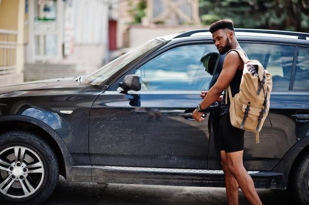 Athlet mit rucksack gegen sein schwarzes geländewagen vor dem training