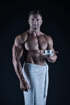 Athlet mit sixpack und bauchmuskeln. sport und fitness. körperhygienekonzept. bodybuilder nackter körper. morgen kaffee. sexy sportler wischen körpertuch nach der dusche ab. mann mit muskulöser passform, nacktem oberkörper.