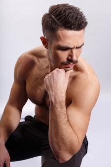 Athlet, muskelmann mit schnurrbart, ohne hemd, mit muskulösem körper, bizeps und trizeps, sitzend auf einem baumstamm, über weißem hintergrund. vertikale ansicht.