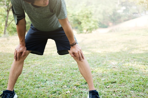 Athlet ruht auf grünem glas im park bei sonnenuntergang nach dem laufen mit flasche wasser (vorsätzliche sonnenblendung und vintage-farbe).