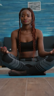 Athlet schlanke frau, die sich während des fitness-morgen-trainings im wohnzimmer in lotusposition auf yoga-karte setzt