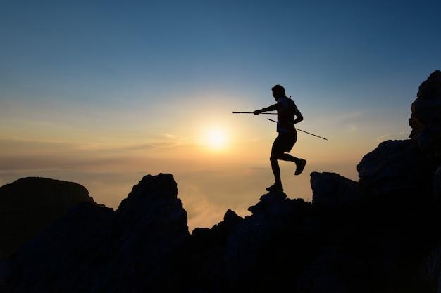 Athlet skyrunner in der silhouette auf den abfahrtsfelsen