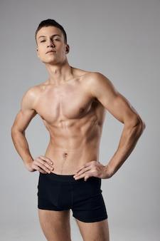 Athleten in schwarzen shorts und mit einem aufgepumpten torso, der hände auf einer abgeschnittenen ansicht des gürtels hält.
