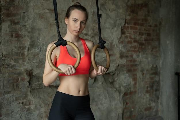 Athletenfrau, die turnringe an der turnhalle hält