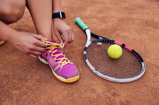 Athletenfrau, die zum spielen eines spiels von tennis, schnürsenkel binden fertig wird.