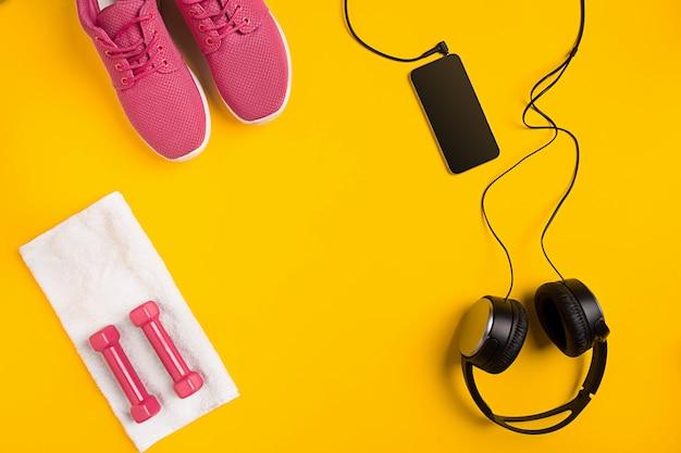Athletensatz mit weiblicher kleidung, hanteln und flasche wasser auf gelbem hintergrund. draufsicht. stillleben