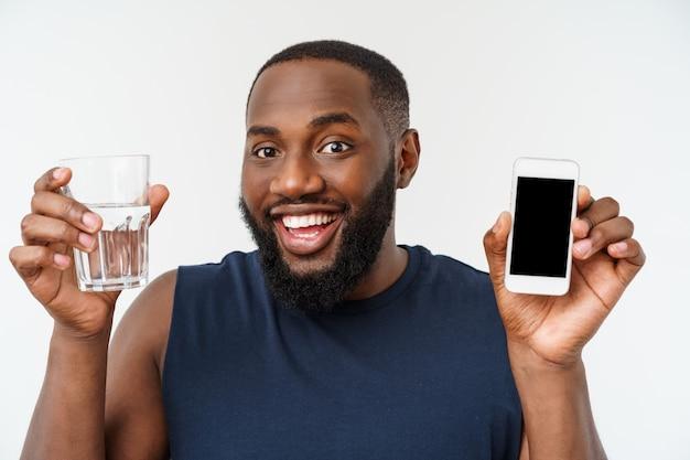 Athletensportmann des afroamerikaners männlicher mit laufendem sport mit handy und trinkwasser vom glas.