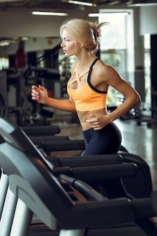 Athletische blonde frau, die auf dem laufband im fitnessstudio läuft