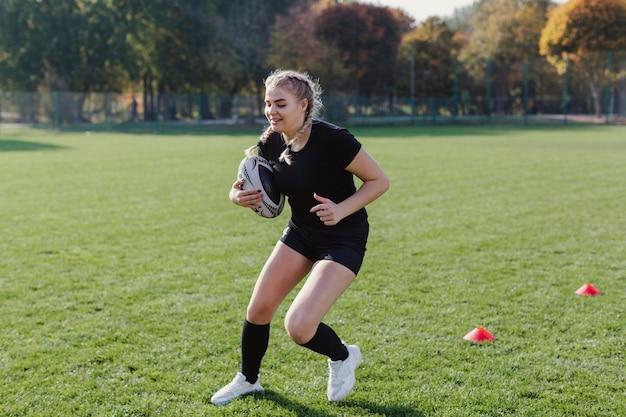 Athletische blonde frau, die eine fußballkugel anhält