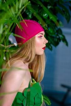Athletische blonde frau mit make-up in badekappe und anzug im schwimmbad mit grünpflanzen