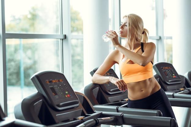 Athletische blonde frau trinkt wasser auf dem laufband im fitnessstudio.