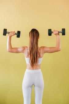 Athletische bodybuilderfrau mit dummköpfen. brunettemädchen in den weißen strumpfhosen, die gewichte auf gelber wand anheben